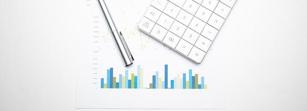 Calculadora com caneta sobre dados financeiros. conceito de pesquisa financeira e de negócios.