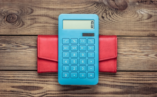 Calculadora com carteira de couro na mesa de madeira. cálculo de custos de compras