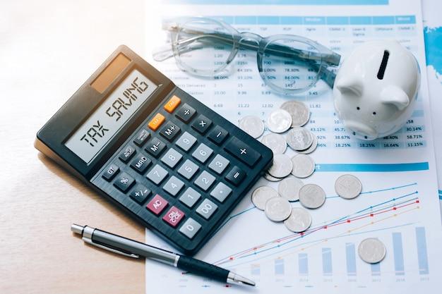 Calculadora com economia de imposto de texto. calculadora, cofrinho, moedas, gráfico de negócios e caneta na mesa de madeira. conceito de economia de dinheiro para contabilidade financeira