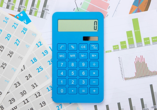 Calculadora com gráficos e tabelas, calendário mensal close-up. cálculo econômico, custeio