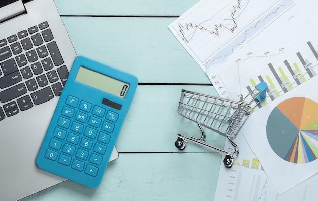 Calculadora com laptop, gráficos e tabelas com carrinho de compras em uma madeira azul.