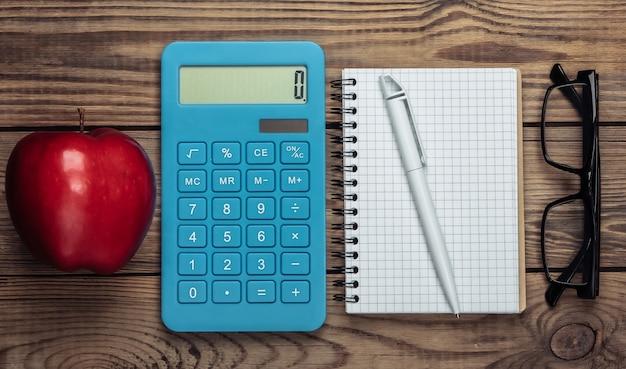 Calculadora com maçã vermelha, caderno, óculos em uma madeira
