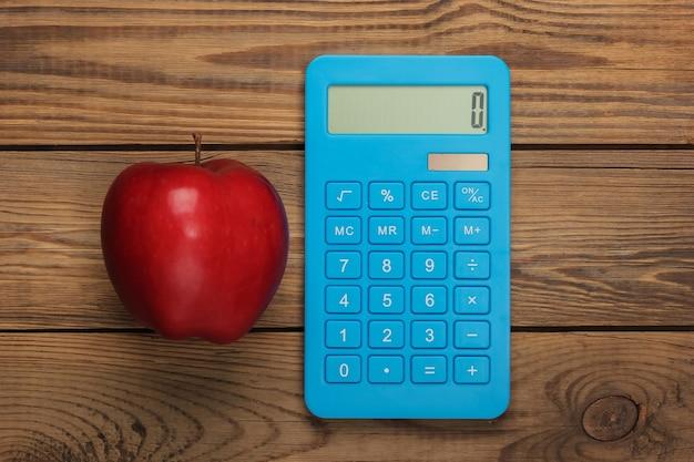 Calculadora com maçã vermelha em uma madeira