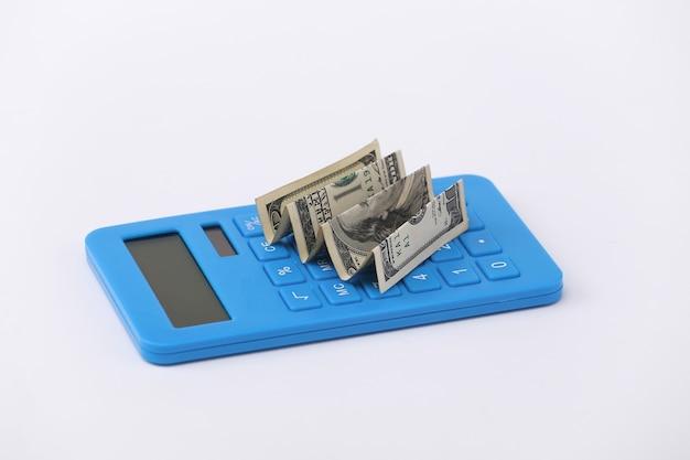 Calculadora com notas de cem dólares em um fundo branco