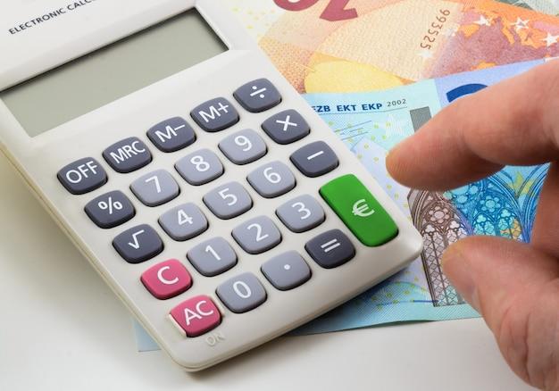 Calculadora com notas de euro e fundo de mão. chave verde com o símbolo do euro.