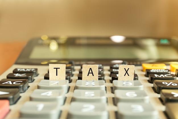 Calculadora com o imposto da palavra escrito no papel conceptual.