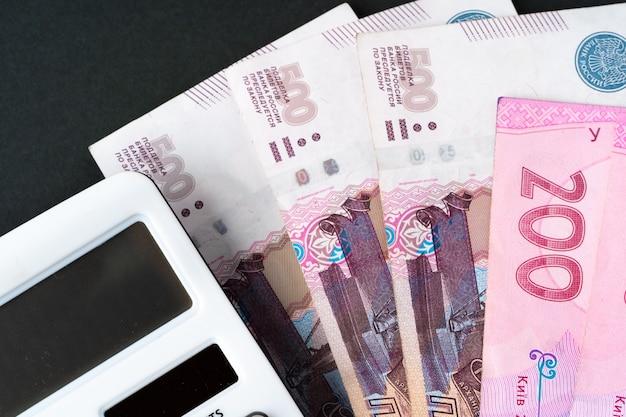 Calculadora com pilha de dinheiro hryvnia ucraniano