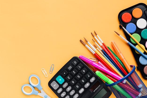 Calculadora com tesoura e ferramentas de desenho espalhadas na mesa amarela