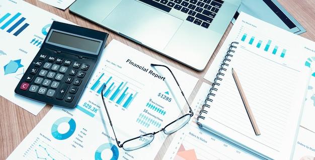 Calculadora de cima, óculos de papel e laptop e na mesa