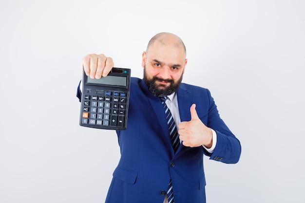 Calculadora de exploração do sexo masculino jovem, aparecendo o polegar na camisa branca, jaqueta e parecendo confiante. vista frontal.