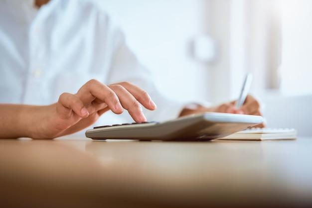 Calculadora de imprensa de mulher para calcular as despesas de renda e planos para gastar dinheiro no escritório em casa.