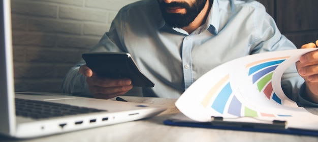 Calculadora de mão de homem com gráfico e teclado na mesa