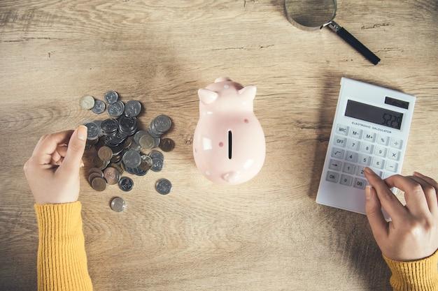 Calculadora de mão de mulher e moeda com cofrinho na mesa