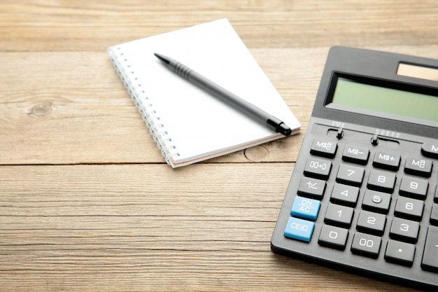 Calculadora de mesa de escritório vista superior com caneta e caderno em cima da mesa para negócios com espaço de cópia.