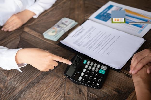 Calculadora de reembolso de empréstimo empregado de banco de mulher mostrando a calculadora para o dono da casa para empréstimo r