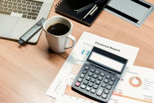 Calculadora de vista superior, papelada, xícara de café e laptop na mesa da sala de reuniões