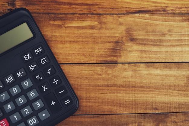 Calculadora do contador colocada sobre uma mesa de madeira