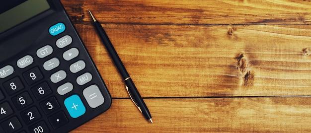 Calculadora do contador com uma caneta preta em uma mesa de madeira