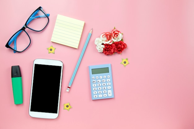 Calculadora do telefone móvel amarelo notebook e óculos husk marcador azul no estilo pastel de fundo rosa com traçado de recorte flatlay copyspace na tela moblie