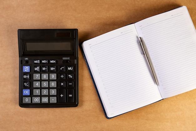 Calculadora e agenda de negócios, caderno ou planejador com caneta bolpoint prata.