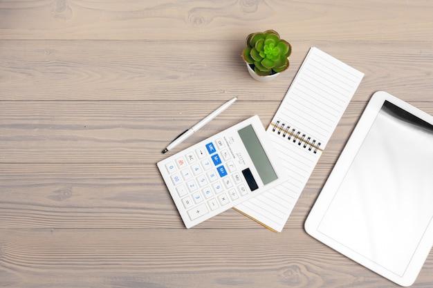 Calculadora e bloco de notas aberto close-up na mesa de madeira