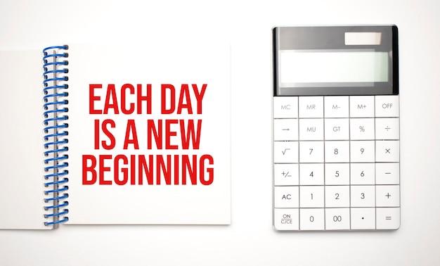Calculadora e bloco de notas com texto cada dia é um novo começo