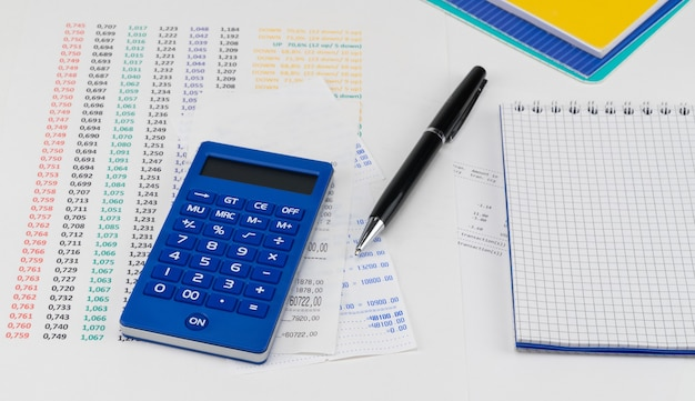 Calculadora e bloco de notas em cima do recibo do supermercado. conceito de compras e pagamento