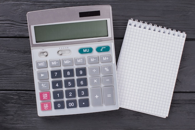 Calculadora e bloco de notas na mesa de madeira escura. vista superior plana lay.