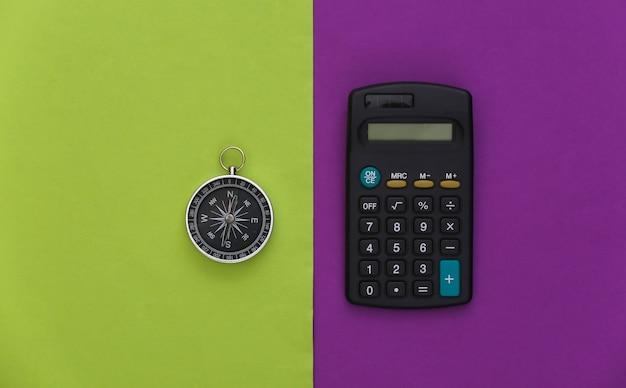 Calculadora e bússola em fundo verde roxo. conceito de negócios. vista do topo