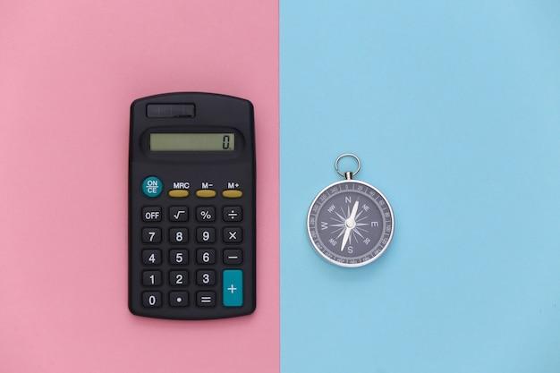 Calculadora e bússola em um fundo pastel rosa azulado. conceito de negócios. vista do topo