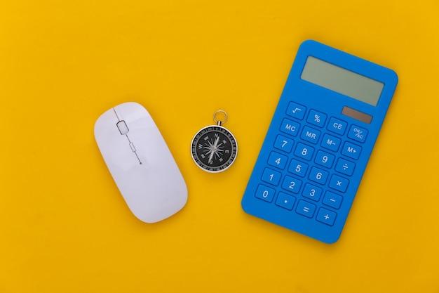 Calculadora e bússola, mouse do pc em fundo amarelo. conceito de negócios. vista do topo