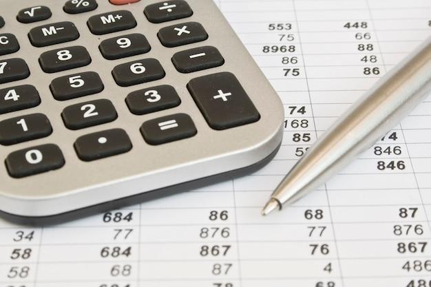 Calculadora e caneta em documentos comerciais