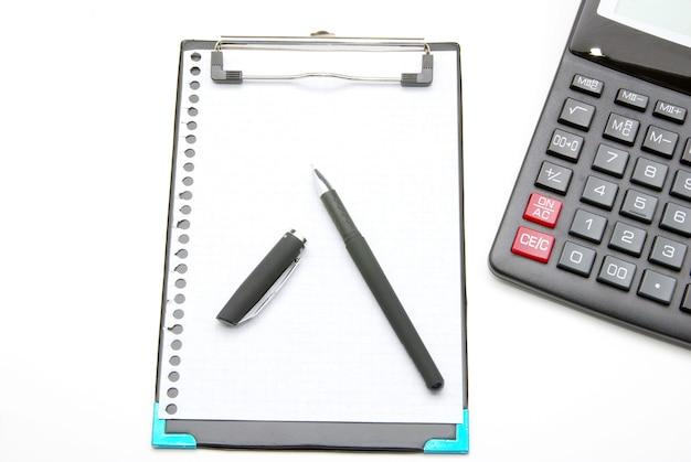 Calculadora e caneta em um fundo branco