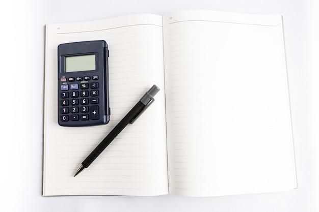 Calculadora e caneta em um livro em branco