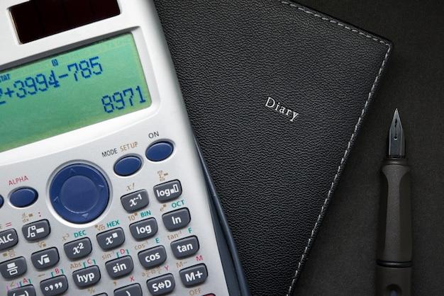 Calculadora e caneta no notebook close-up