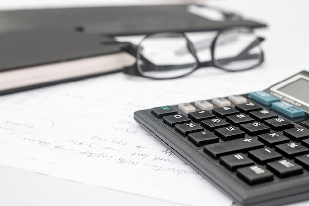 Calculadora e documentos para trabalhar na mesa, finanças e economia, conceito de negócio.