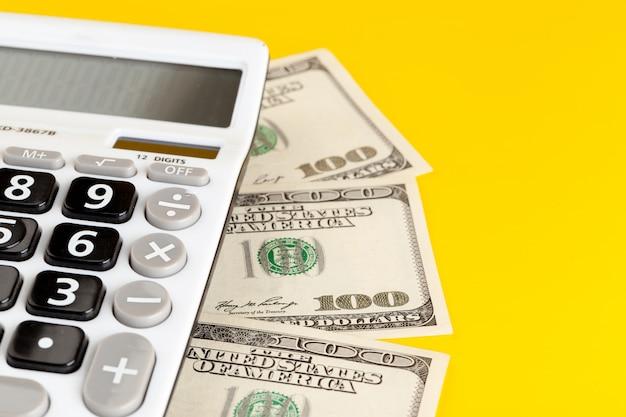 Calculadora e dólares em amarelo