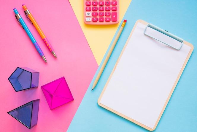 Calculadora e formas geométricas perto de material escolar