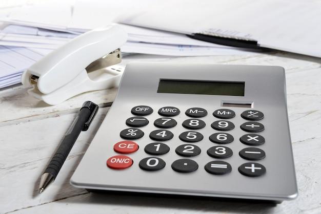 Calculadora e grampeador em uma mesa de madeira branca