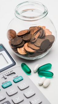 Calculadora e moedas de 1 centavo em frasco de vidro no fundo branco, o símbolo do custo de saúde