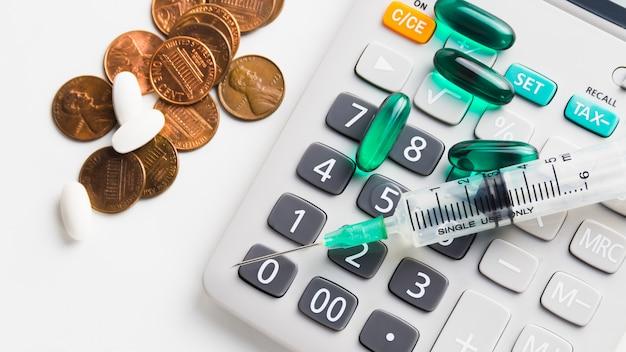 Calculadora e moedas de 1 centavo em fundo branco com comprimidos, o símbolo do custo de saúde