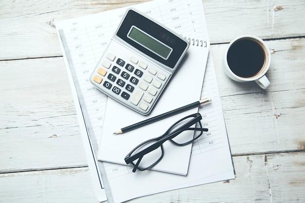 Calculadora e óculos em documentos na mesa