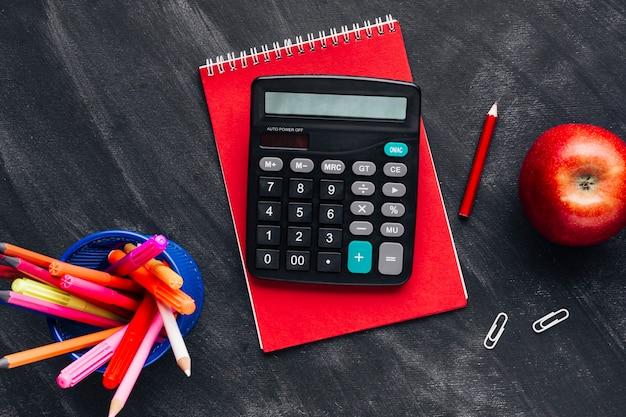 Calculadora e papelaria no quadro-negro