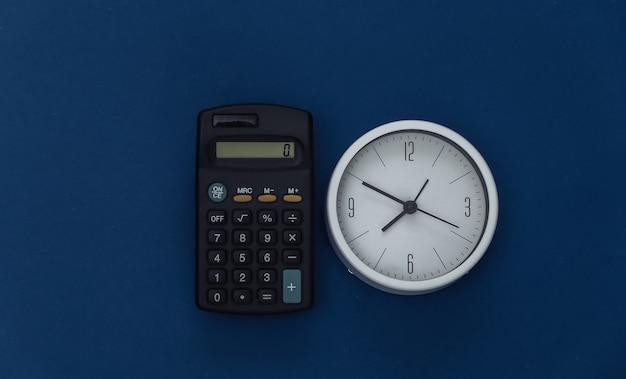 Calculadora e relógio no fundo azul clássico. cor 2020. vista superior.