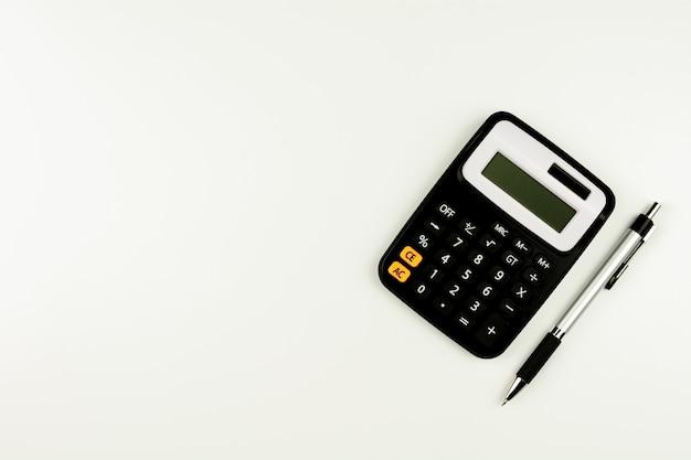 Calculadora ee uma caneta na mesa branca