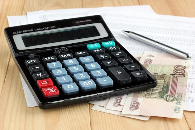 Calculadora eletrônica, caneta metal e dinheiro russo em folhas de papel com números.