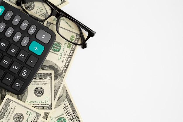 Calculadora em cima de notas de dólar com cópia-espaço