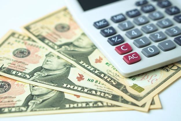 Calculadora em notas de dez dólares em um fundo branco