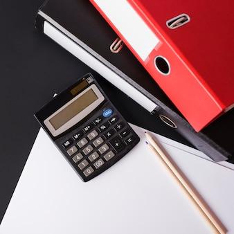 Calculadora; lápis; arquivos de papel e papel em fundo preto