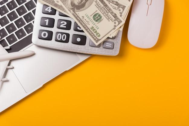 Calculadora, laptop, avião de brinquedo, mouse e notas de dólar